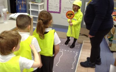 """This week we had a lady come into our class to talk about road safety. She brought a pretend road and she taught us to """"stop, look, listen and think"""" before we crossed. We had the chance to dress up as lolly pop men and ladies and stopped the traffic to let our friends cross the road."""